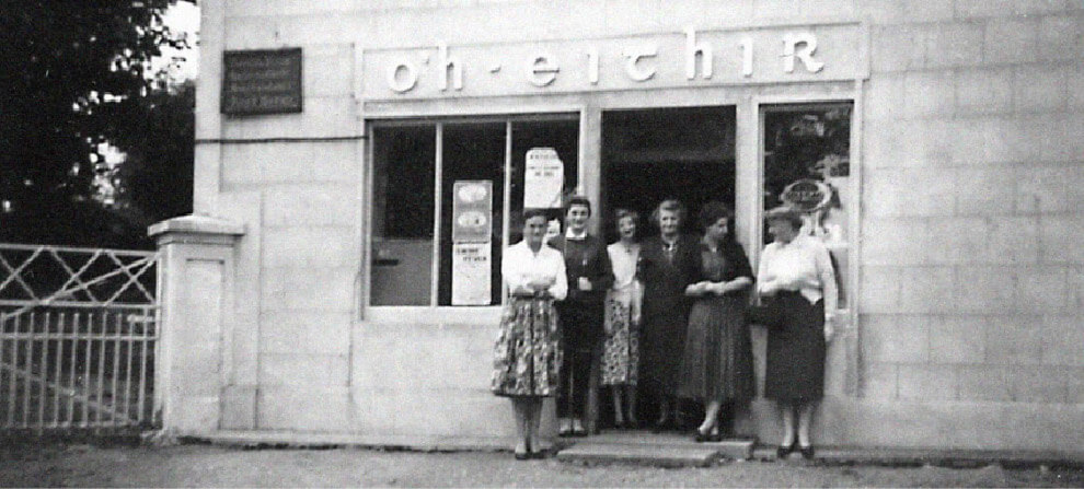 Black And White Historical Image Of Six Women Standing Outside A Bakery