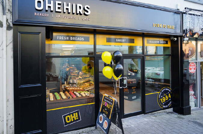 A Shopfront Of O'Hehir's Bakery With Cakes And Donuts In The Window