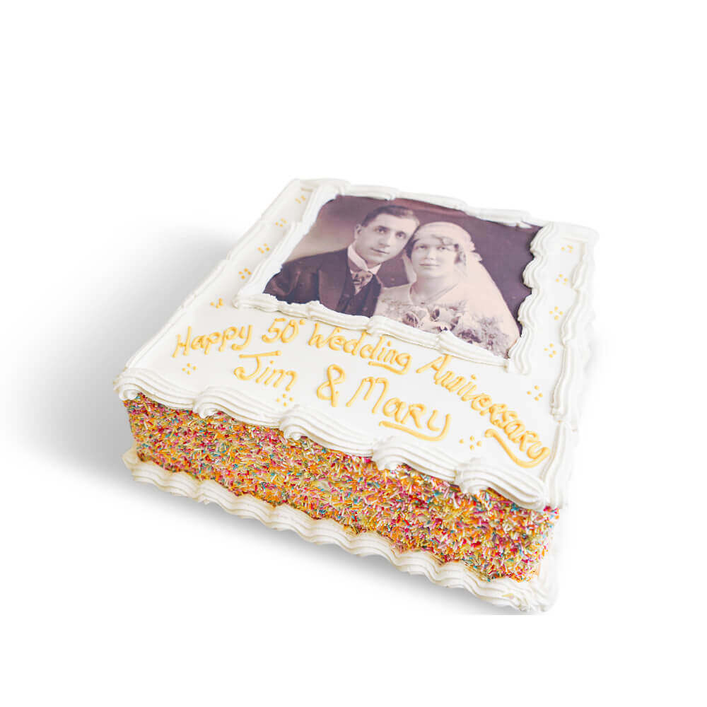 A white anniversary cake with a wedding photo and yellow writing