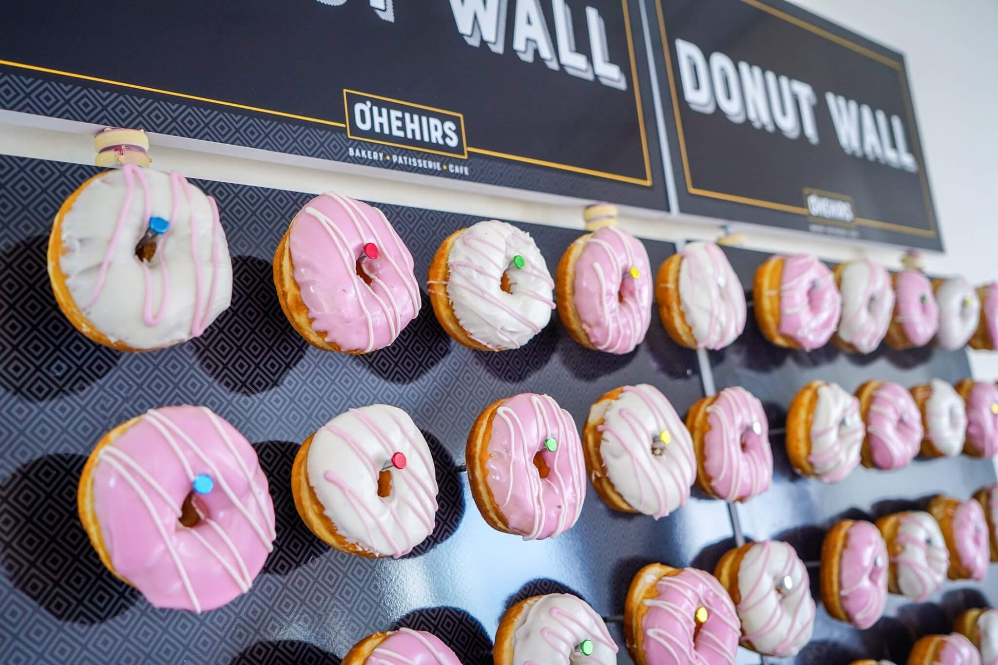 Pink And White Frosted Donuts On Pegs Of A Donut Wall