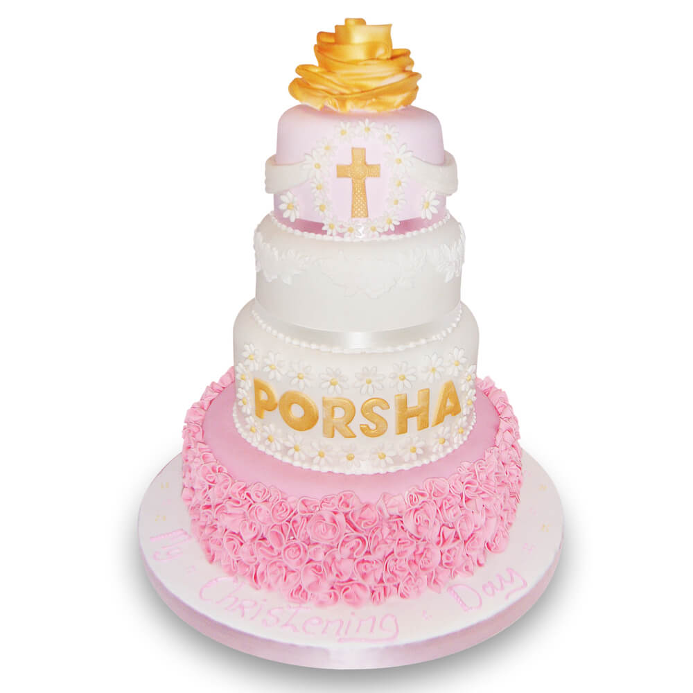 A christening cake with pink and yellow decorations